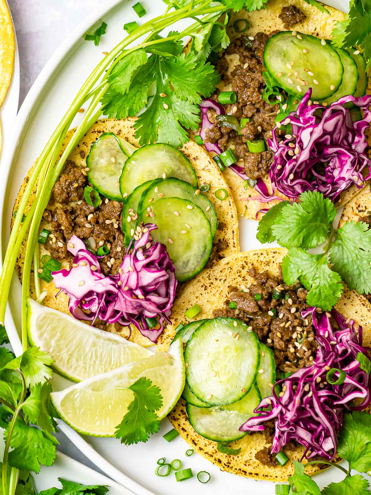 Korean beef bulgogi tacos with cabbage slaw, lime, and pickled cucumbers on a white plate
