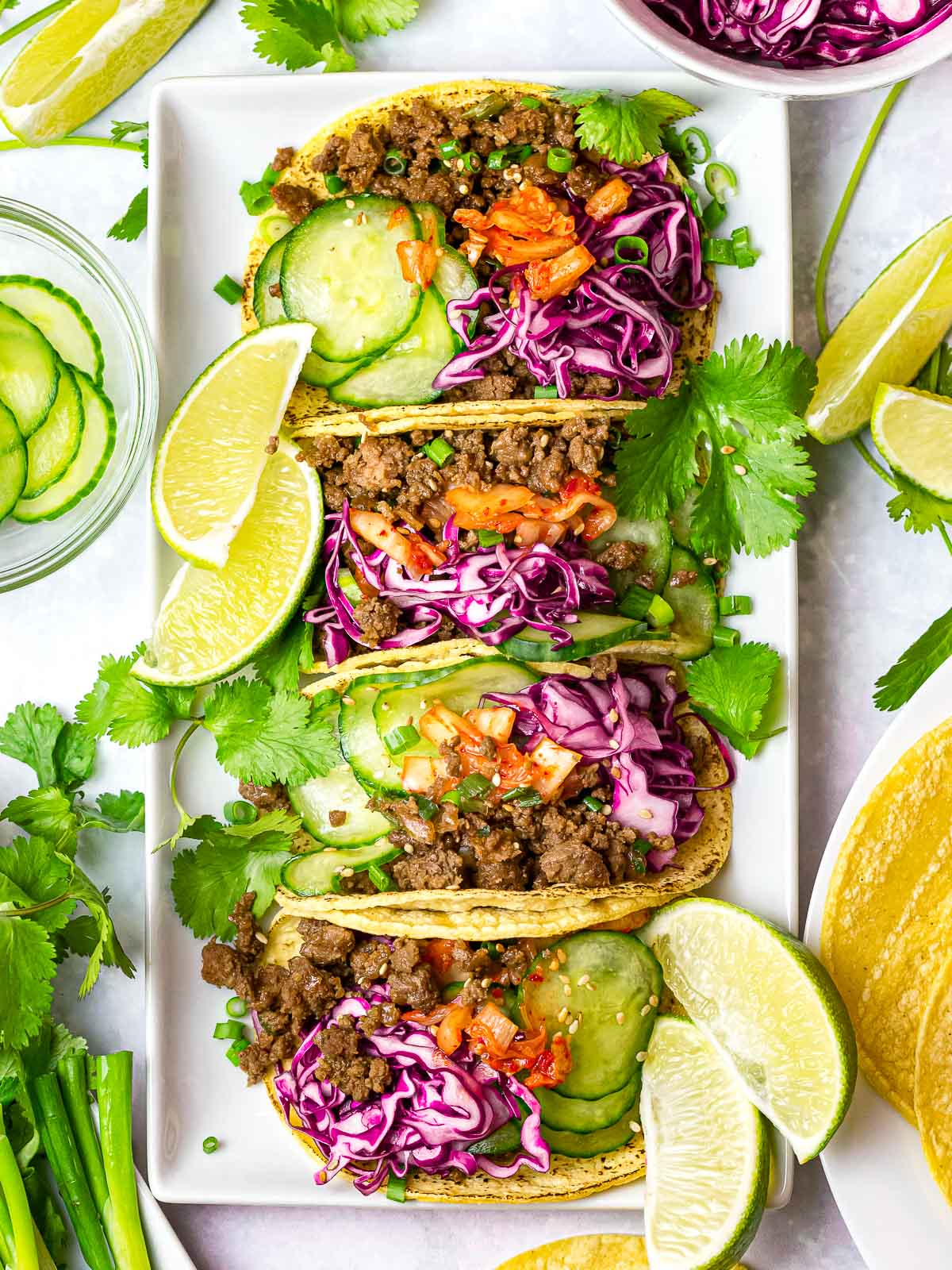 Korean beef tacos with purple slaw, kimchi, cucumbers, and lime on a white plate