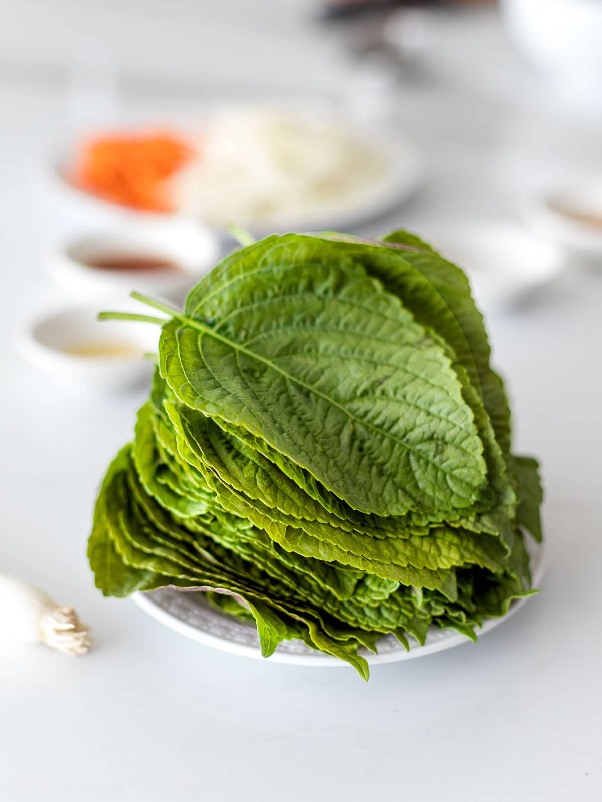 a stack of Korean perilla leaves on a plate