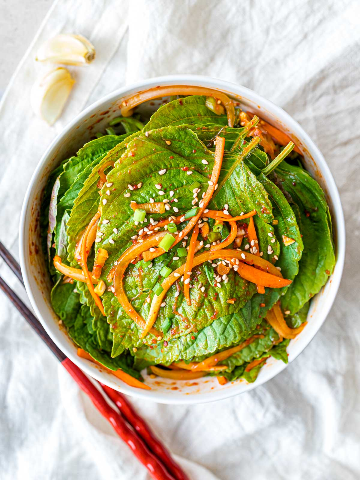marinated Korean perilla leaf kimchi with red pepper flakes and carrots in a white bowl next to red chopsticks