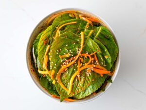 Korean perilla leaf kimchi in a white bowl with shredded carrots and sesame seeds
