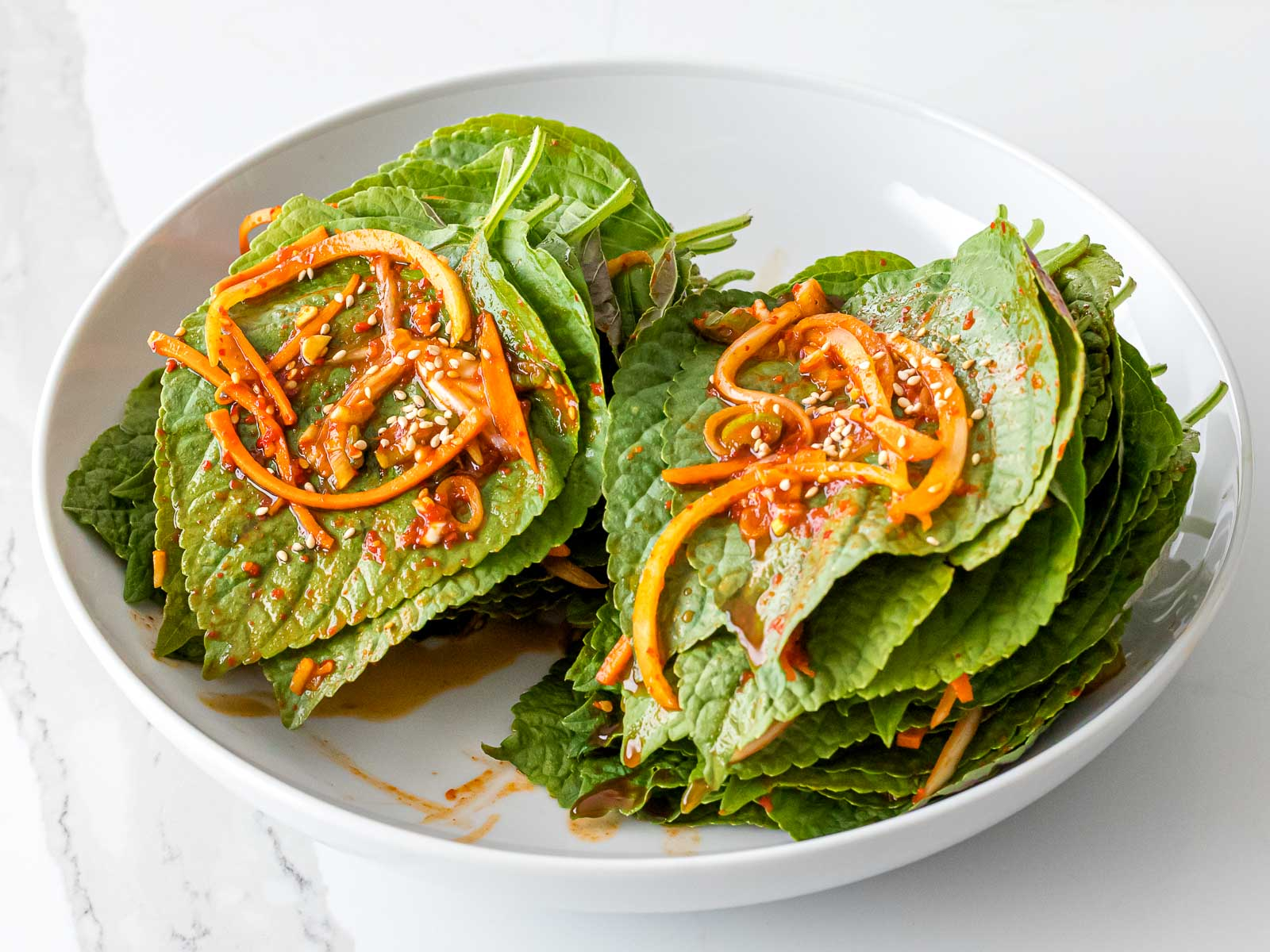 Korean perilla leaves with kimchi marinade in a white bowl