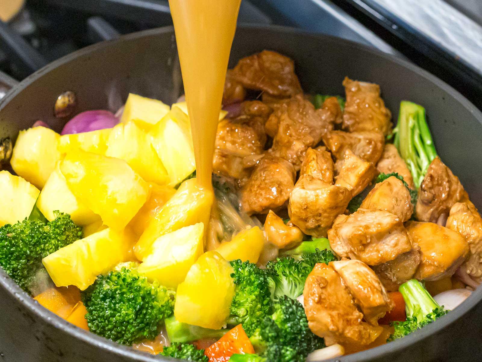 pineapple teriyaki sauce being added to pineapple chicken