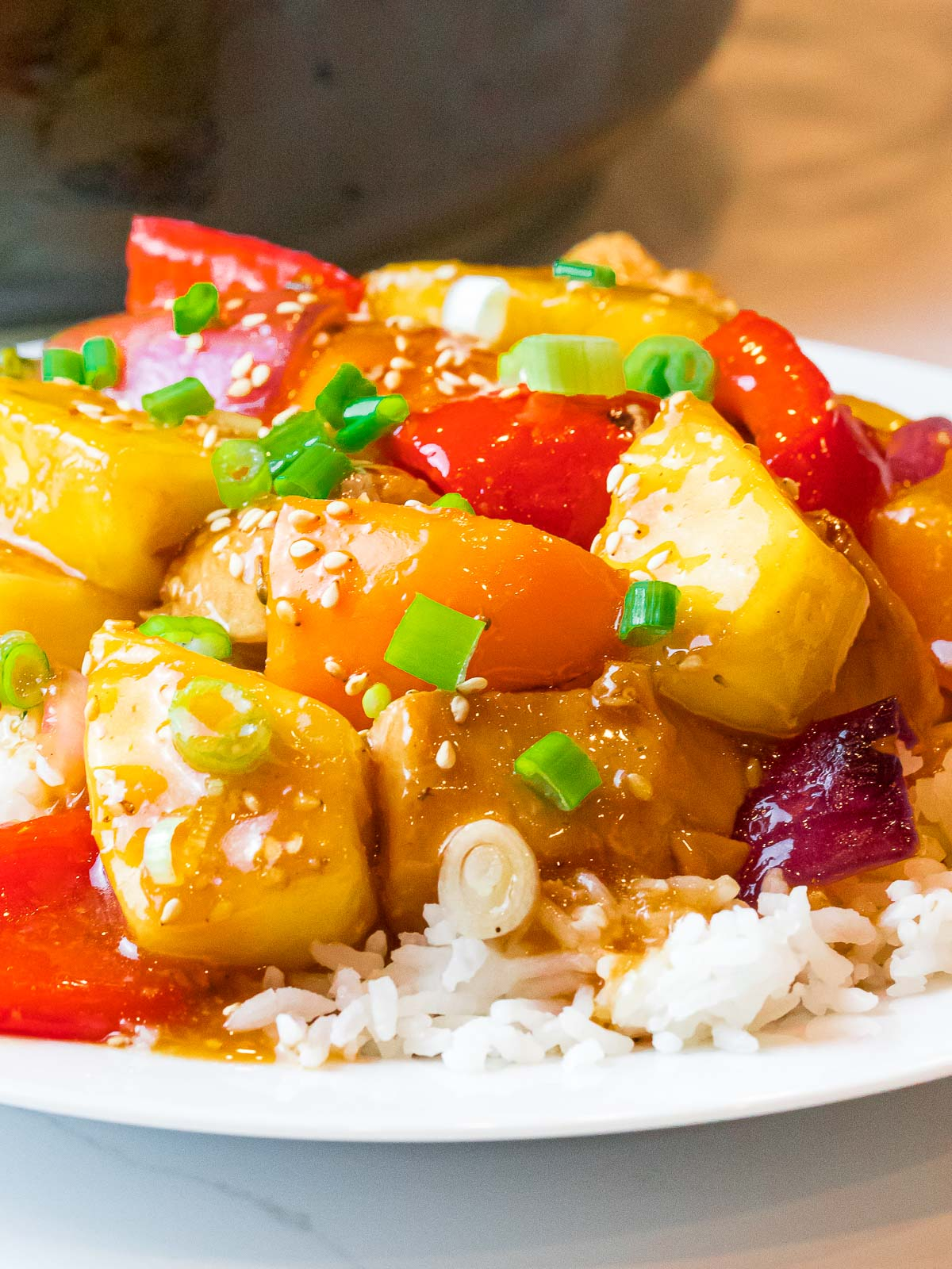 hawaiian pineapple chicken and rice with red peppers and scallions on a plate