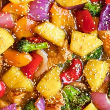 pineapple chicken teriyaki with broccoli, red peppers, and sesame seeds