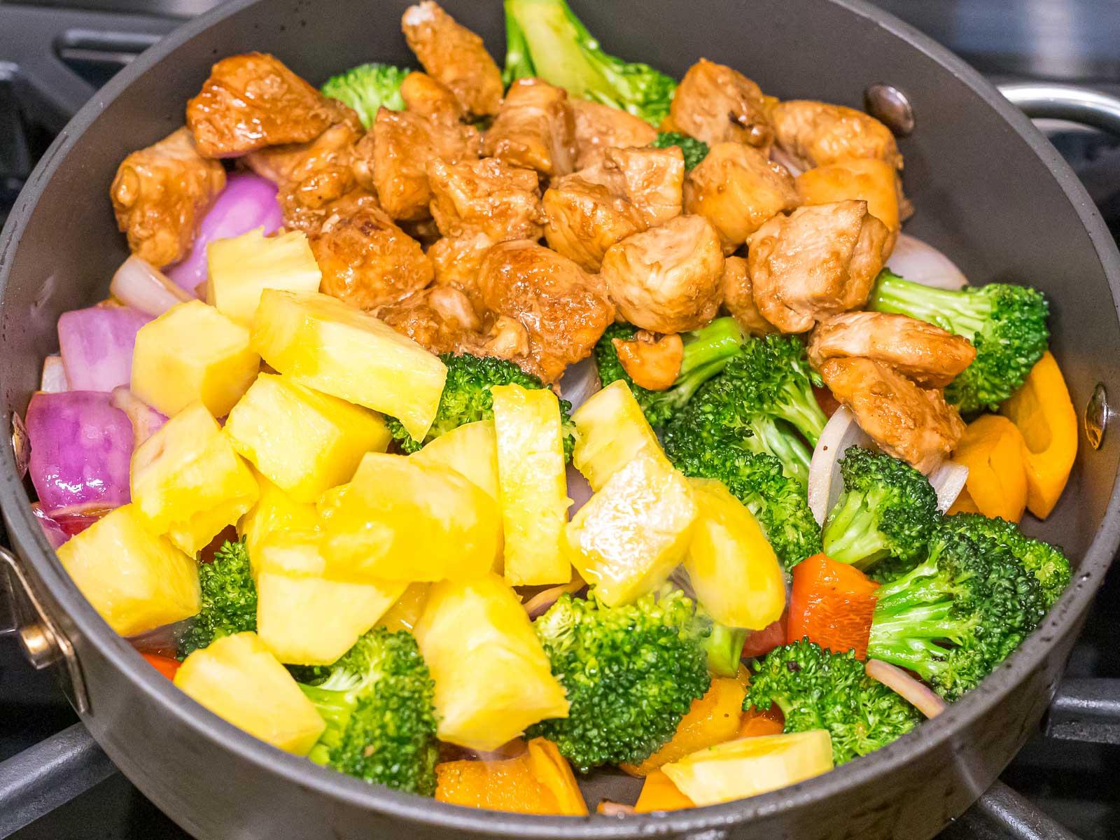 Hawaiian pineapple chunks, chicken, and veggies stir fried together in a pan