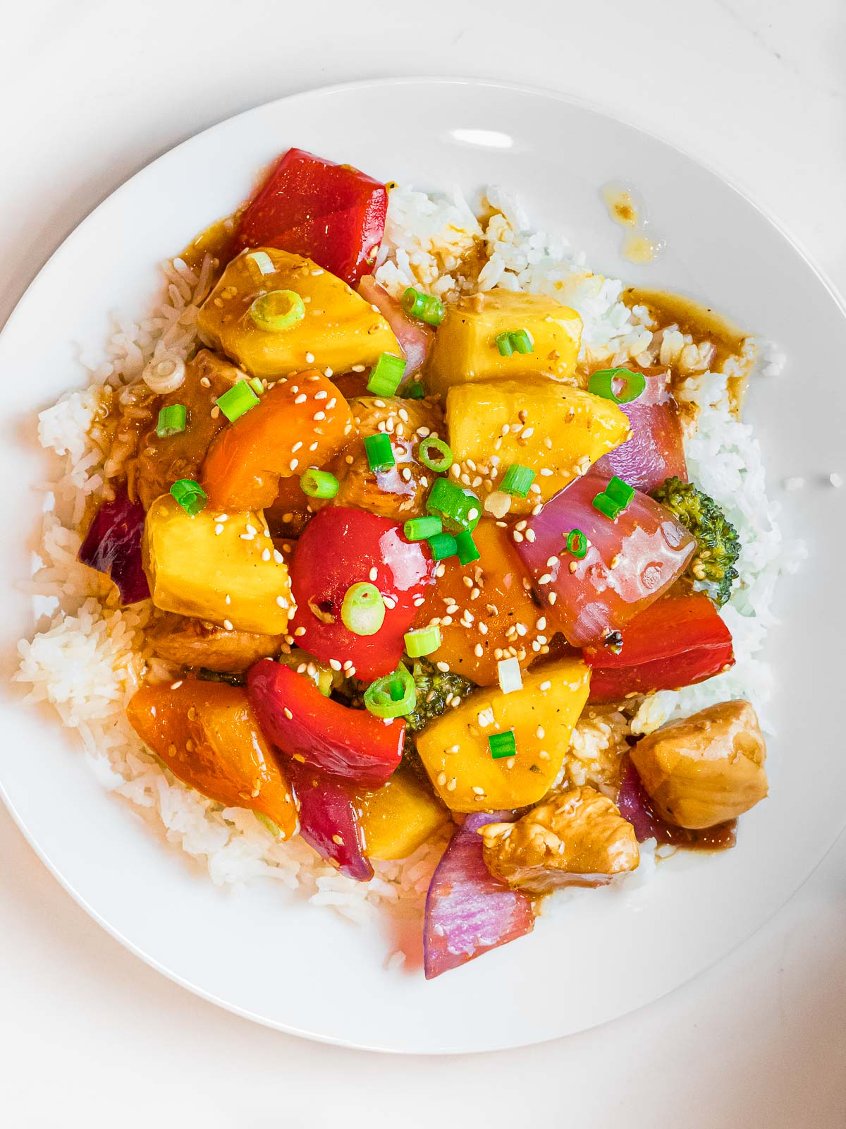 summer pineapple chicken stir fry with red peppers and pineapple chunks over rice