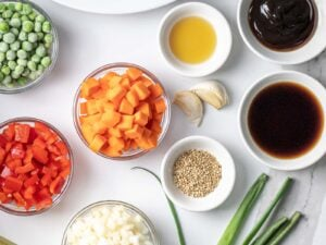 diced carrots, diced red bell pepper, and sauces in little bowls