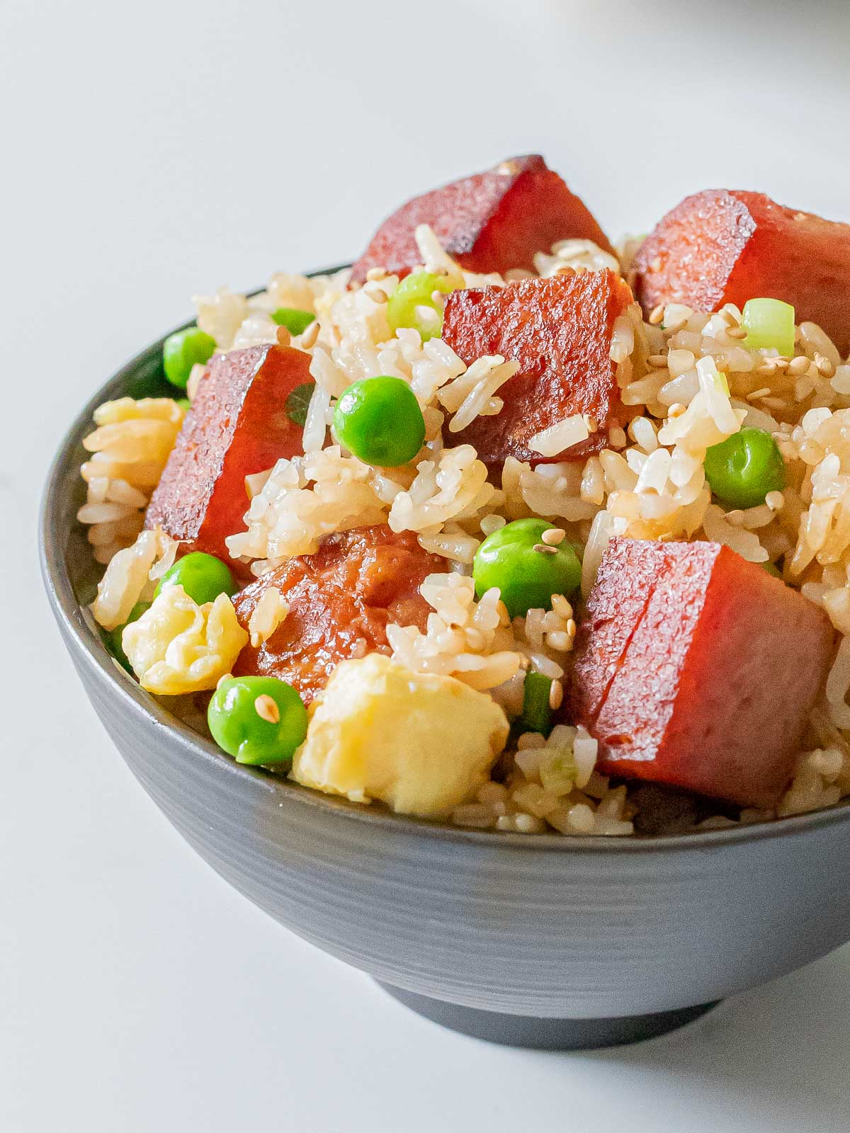 bowl of spam fried rice with eggs, green peas, and crispy cubes of spam