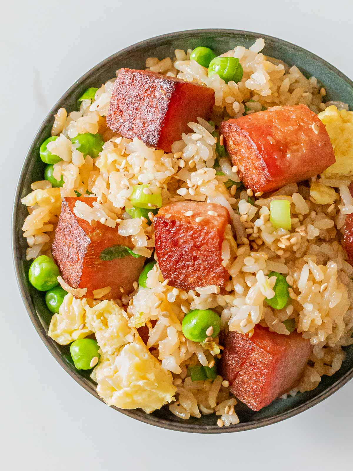 bowl of spam fried rice with crispy cubes of spam, eggs, green peas, and sesame seeds