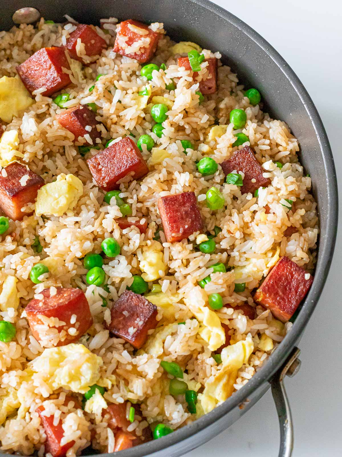 overhead of spam fried rice with pan fried spam, eggs, and green peas in a pan