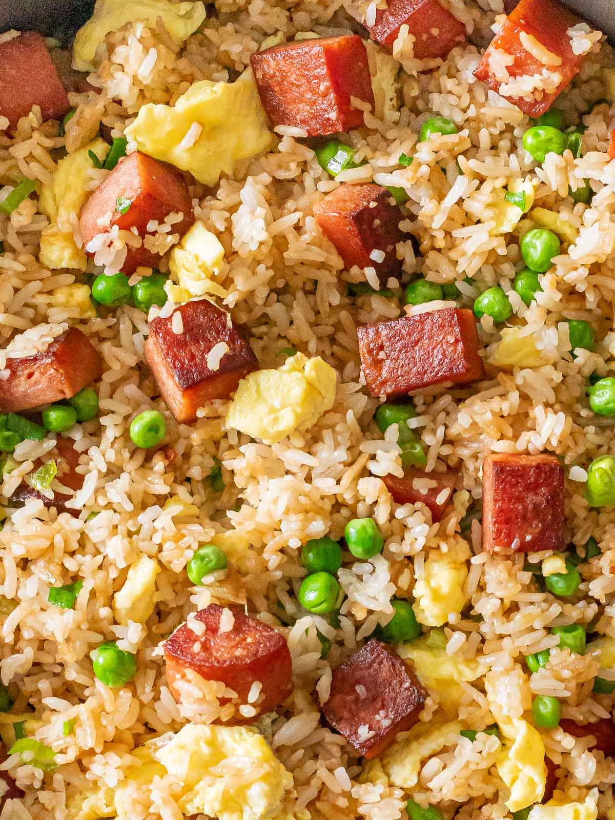 overhead of spam fried rice with eggs and green peas