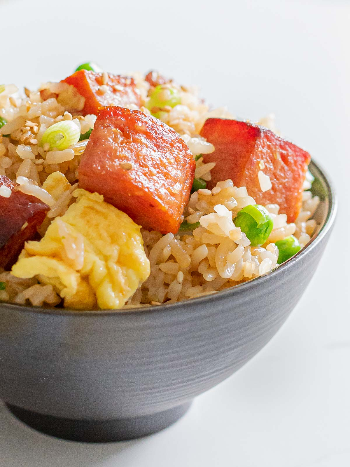 close up of spam fried rice with eggs, green peas, and rice in a dark bowl