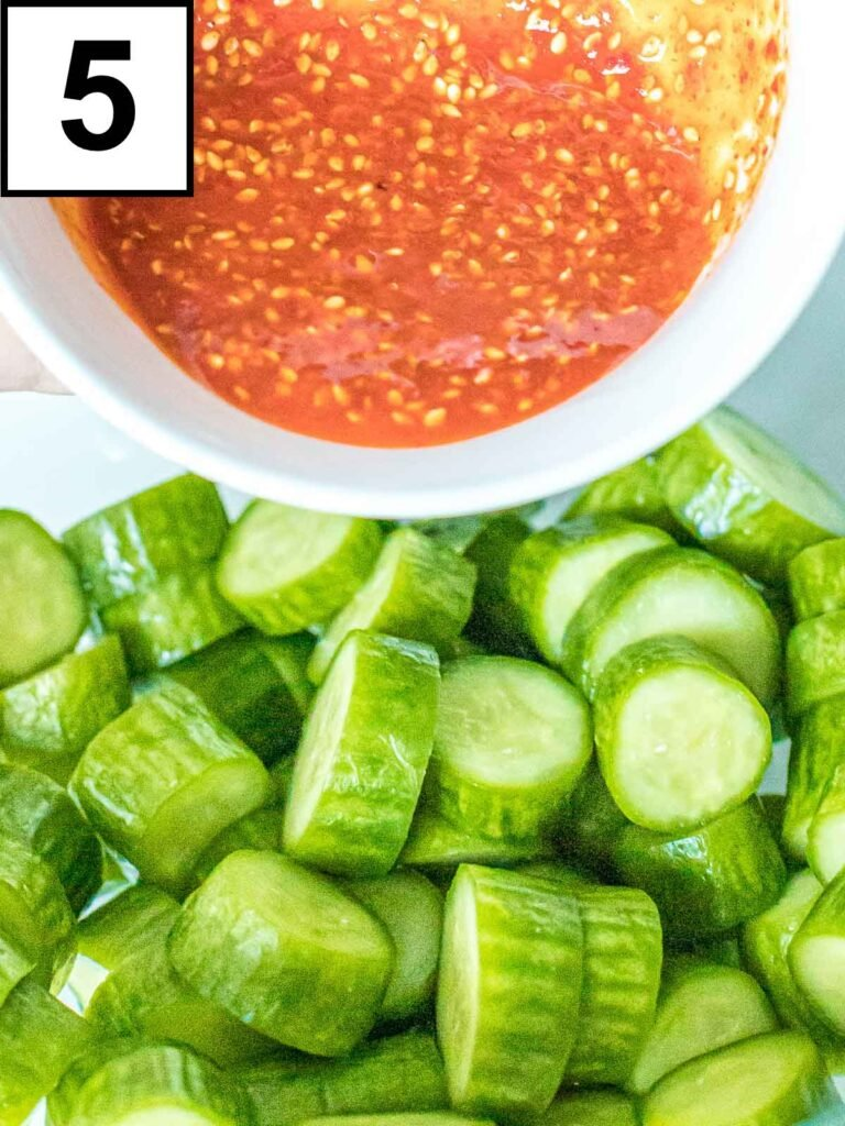 spicy Korean red pepper sauce being poured onto brined cucumbers