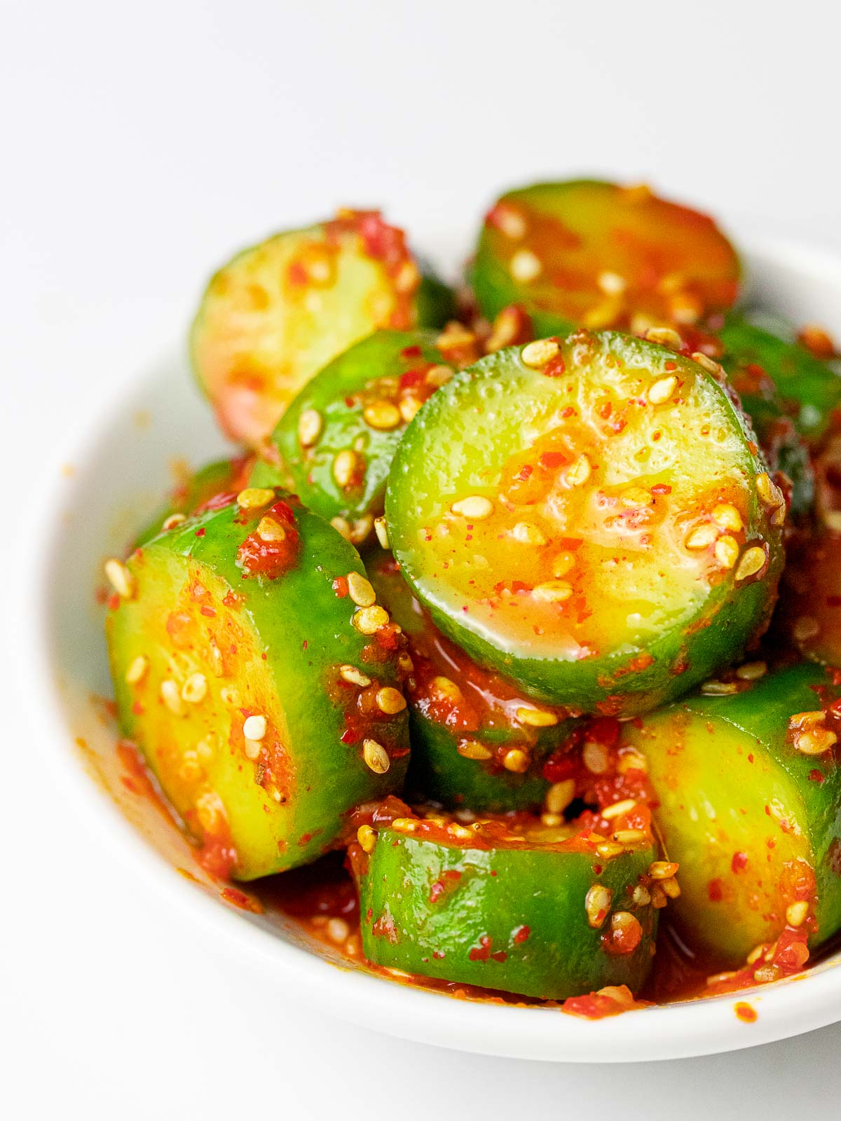 spicy Korean cucumber side dish with sesame seeds on a white plate