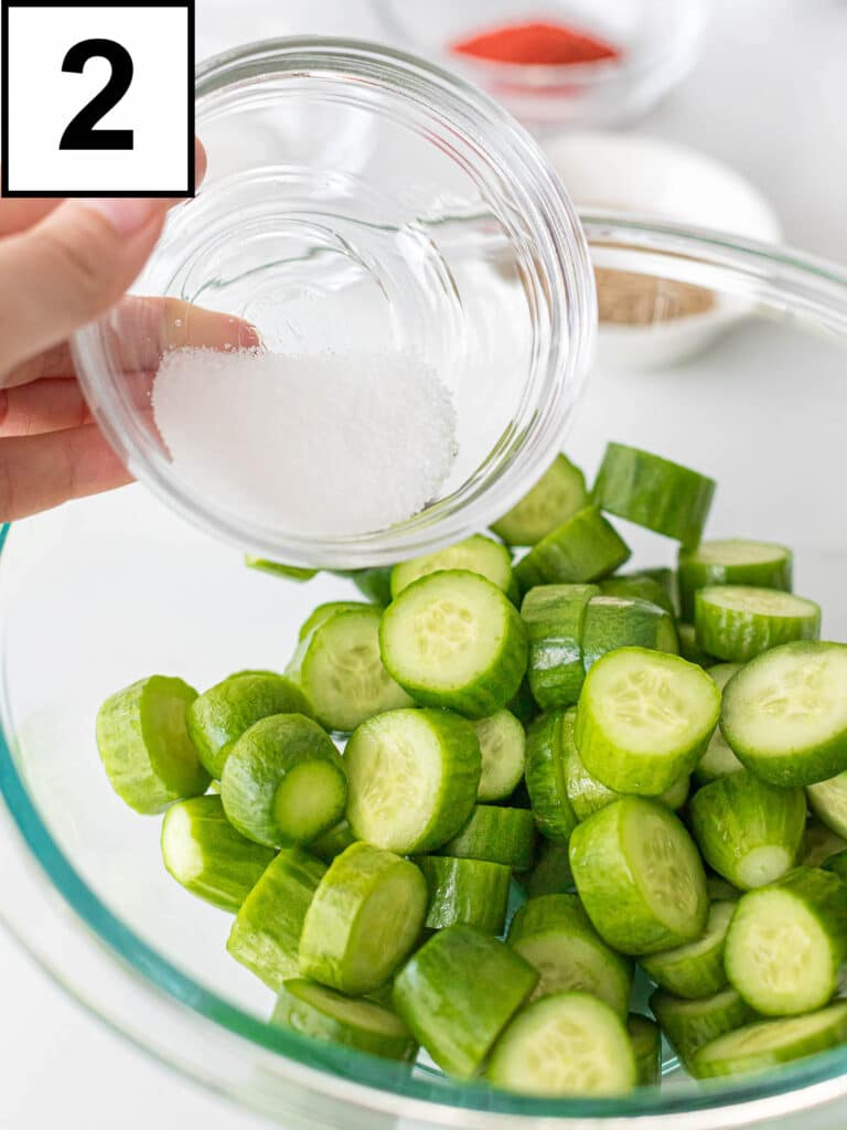 sliced cucumbers in a glass bowl with sea salt