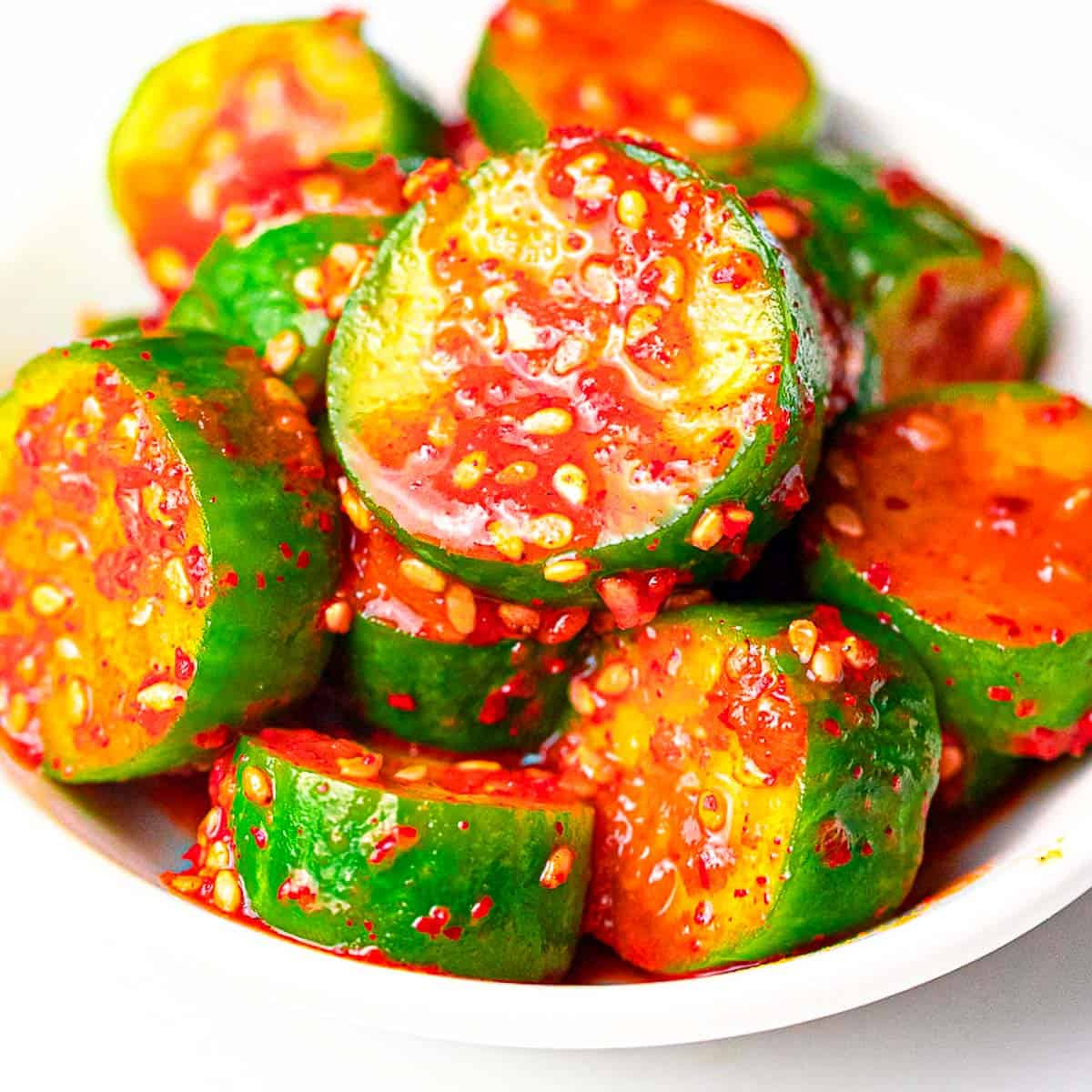 spicy Korean cucumber salad (Oi Muchim) with sesame seeds on a white plate