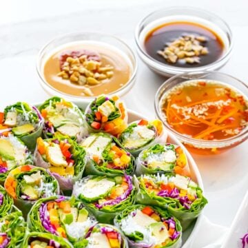 three spring roll sauces next to a plate of spring rolls
