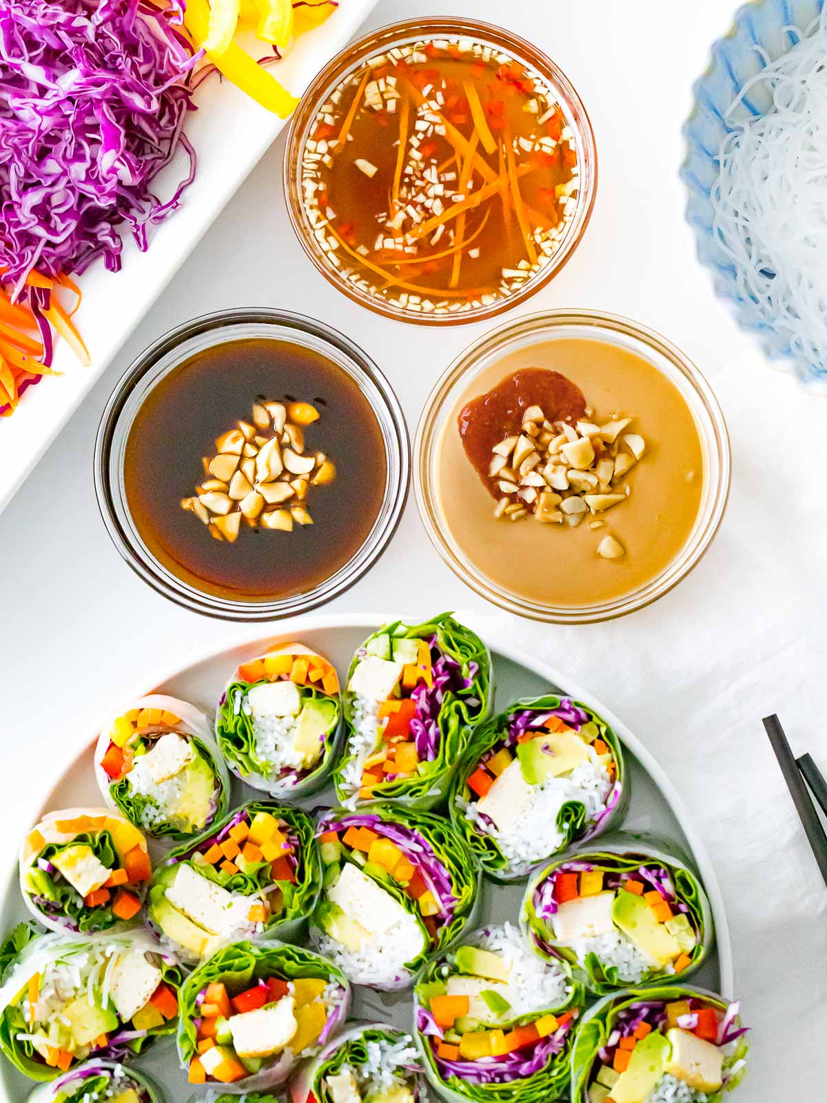 spring roll sauces including peanut sauce, fish sauce, and hoisin next to a plate of spring rolls