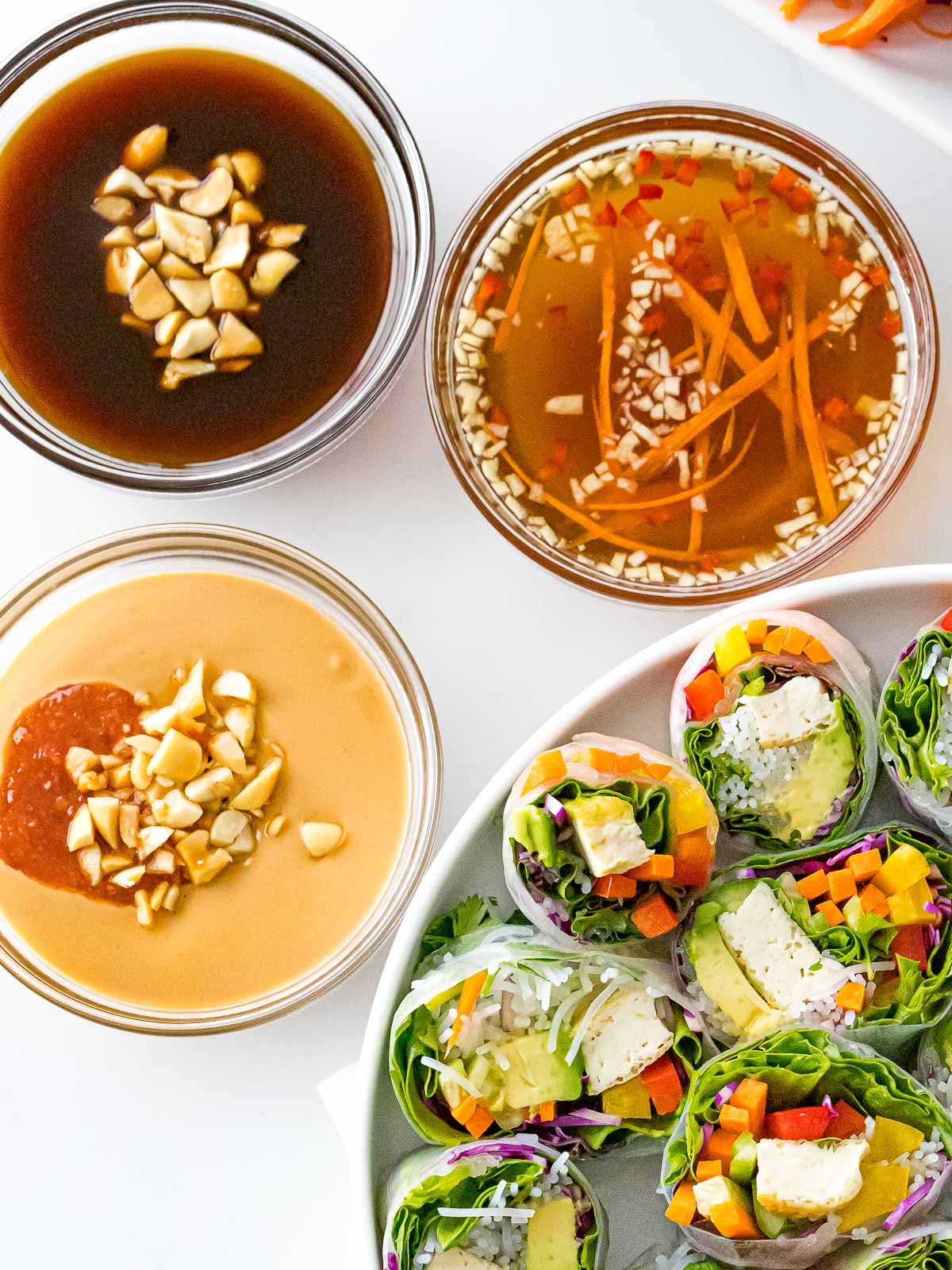spring roll sauces including peanut sauce, hoisin, and fish sauce next to spring rolls