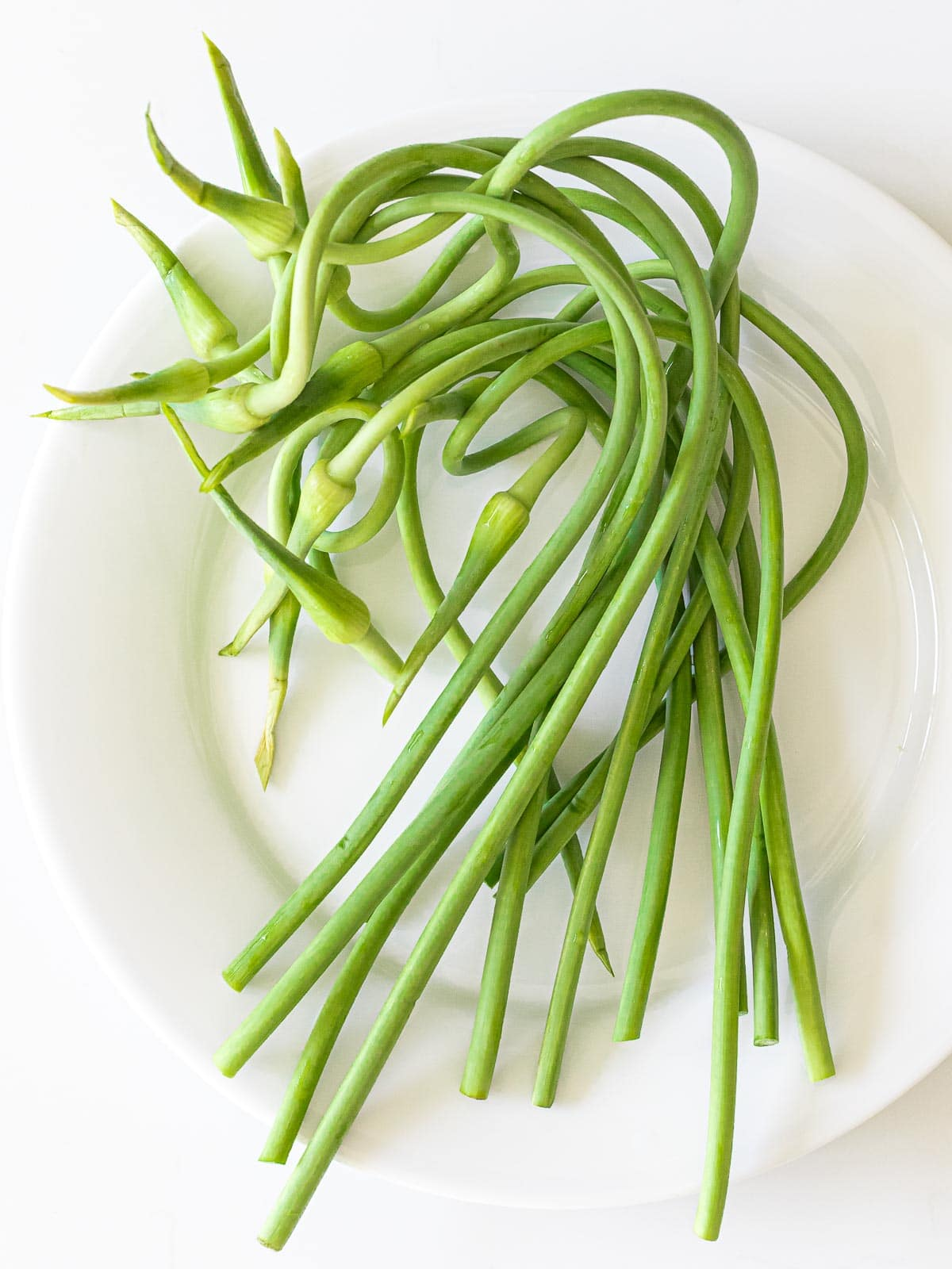 garlic scapes on a white plate