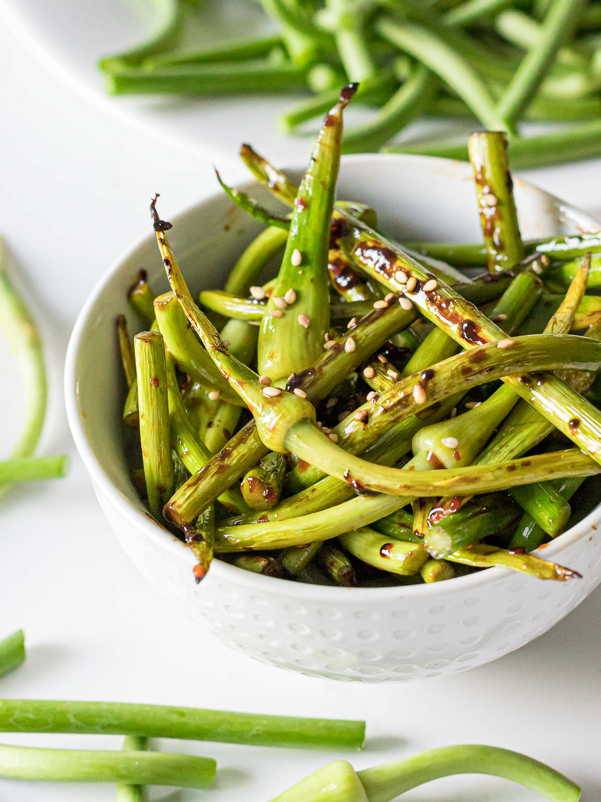 stir fried garlic scapes in a white bowl