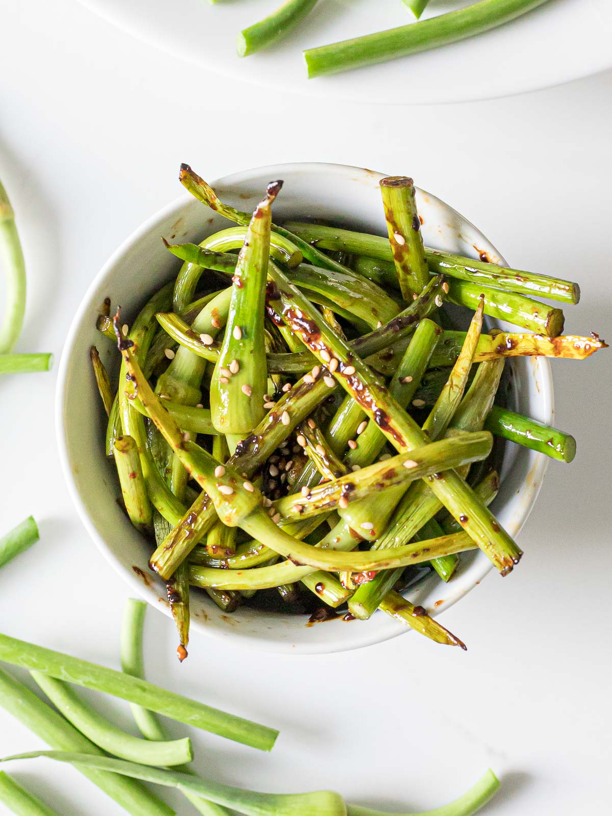 sauteed garlic scapes in a white bowl