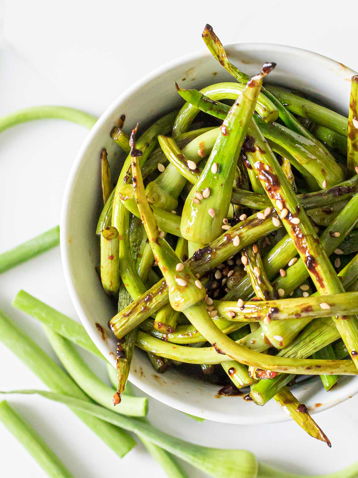 close up of stir fried garlic scapes in a white bowl