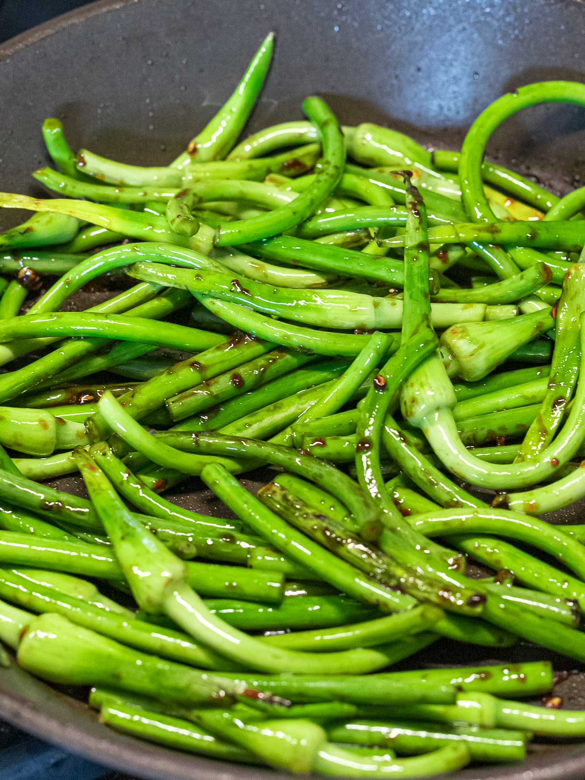 sauteed garlic scapes in a dark pan