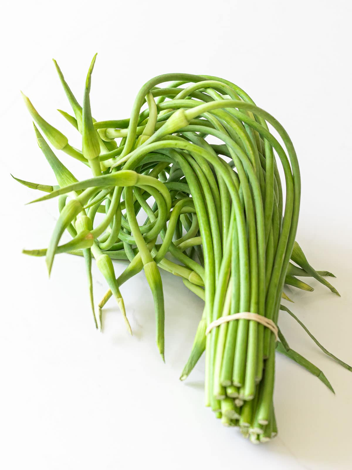 a bundle of garlic scapes on a white surface
