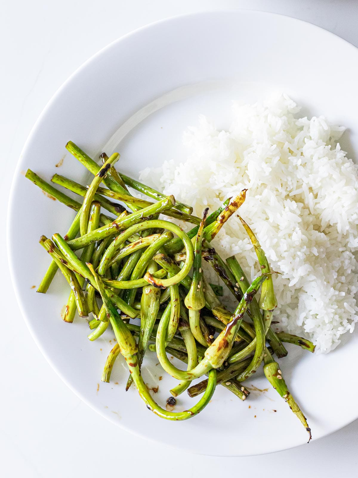 stir fried garlic scapes next to steamed rice on a white plate
