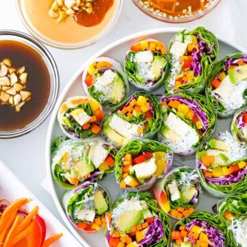 Vietnamese vegetarian summer rolls with rainbow veggies with peanut sauce, hoisin sauce, and dipping sauce
