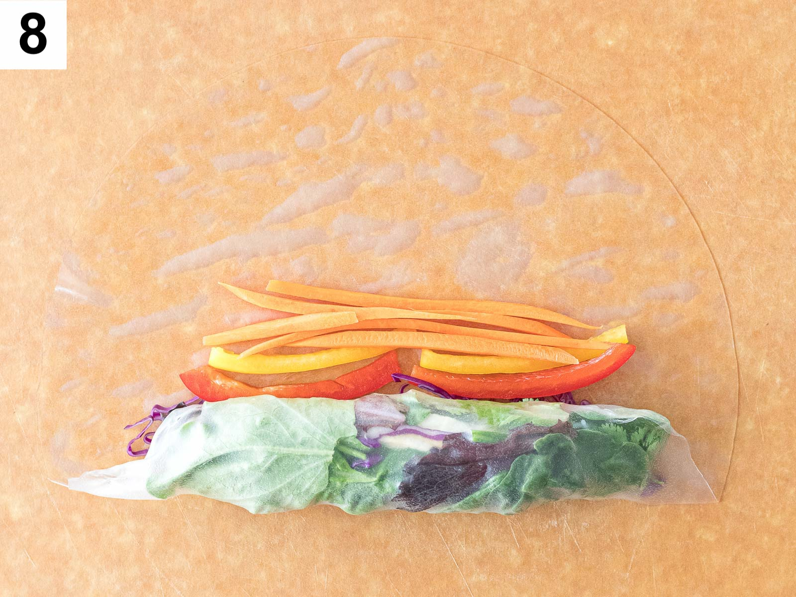 wrapping summer rolls with rice paper and carrots and pepper