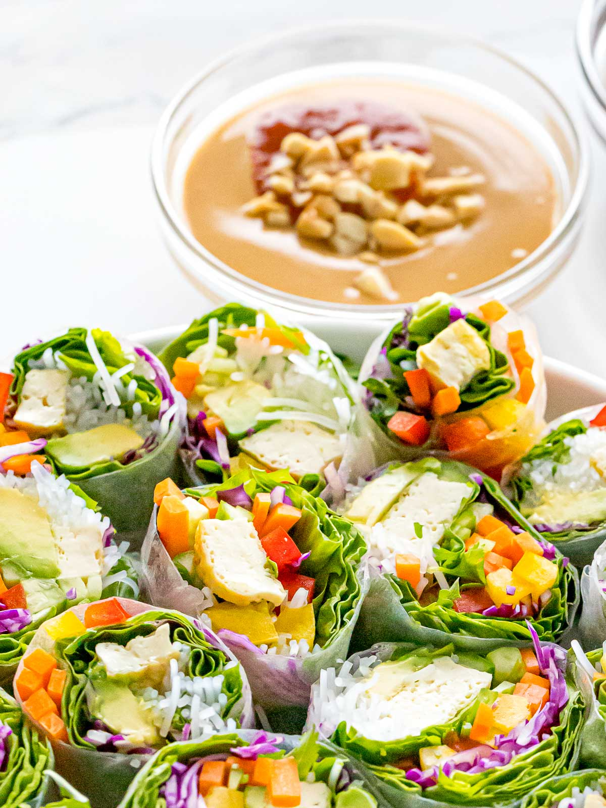 Vietnamese peanut dipping sauce next to a plate of fresh spring rolls