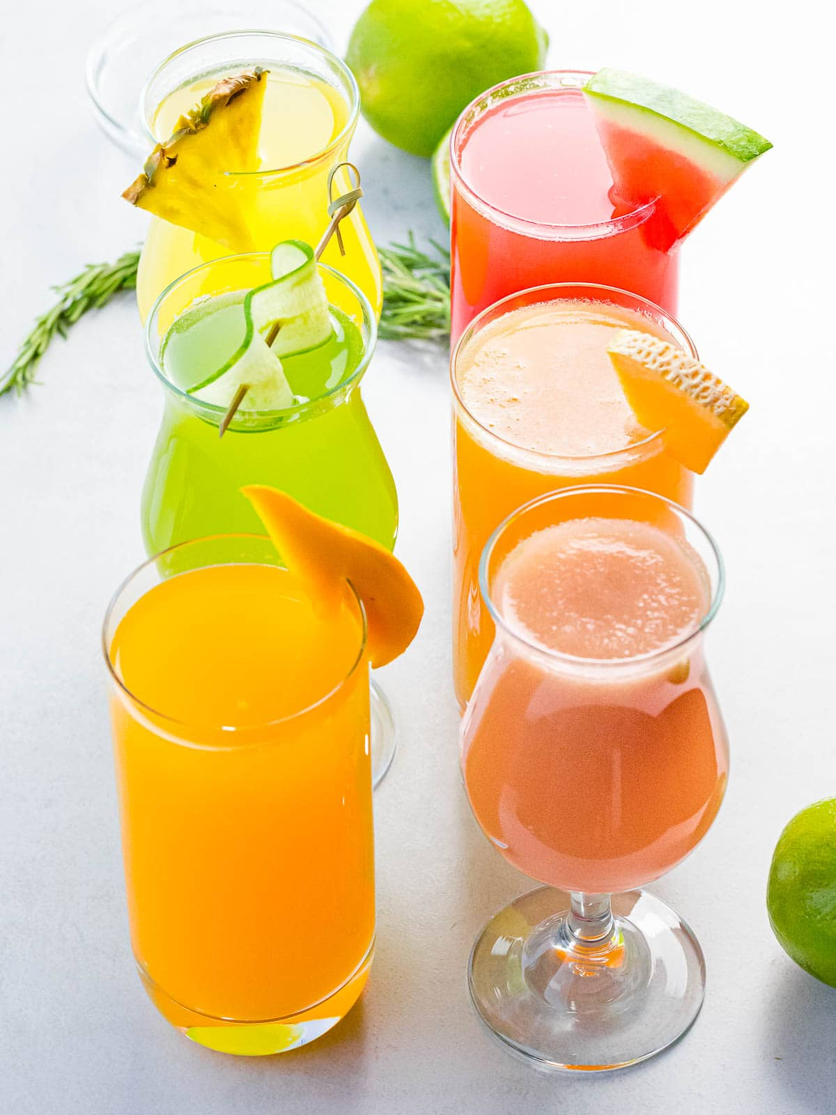 different kinds of fruit flavors of aguas frescas in glasses, including watermelon, cucumber, pineapple, and mango