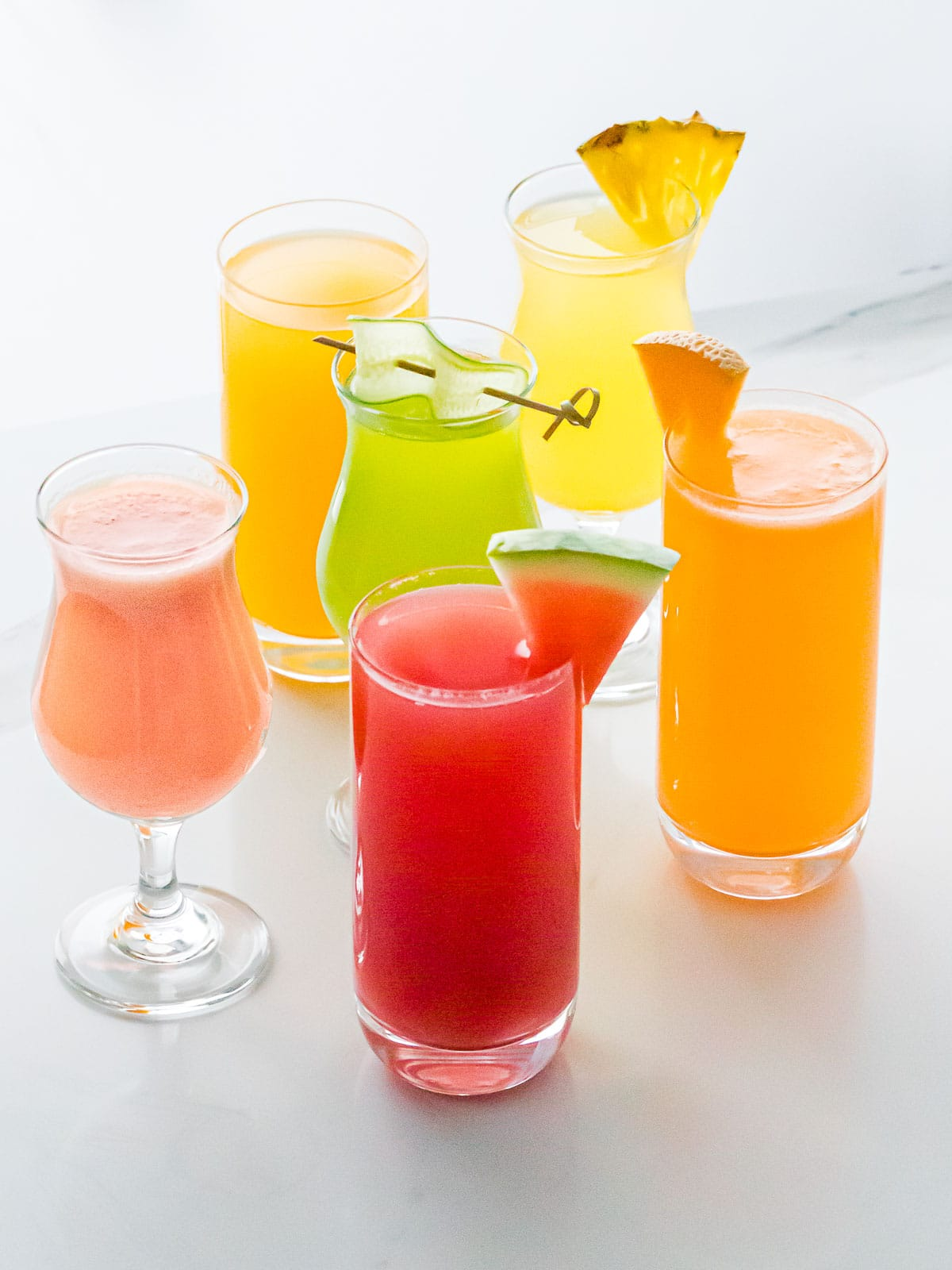 colorful flavors of agua fresca in glasses garnished with watermelon, cucumber, pineapple, and cantaloupe