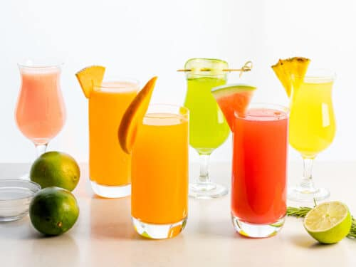 different fruit flavors of aguas frescas including watermelon, cucumber, pineapple, mango, and cantaloupe next to limes