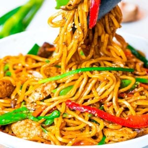 chicken lo mein with red peppers, mushrooms, and scallions picked up by tongs