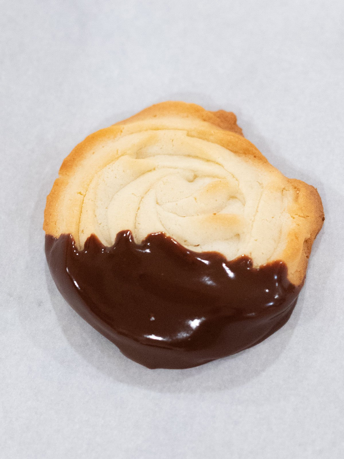 butter cookie dipped in chocolate on parchment paper
