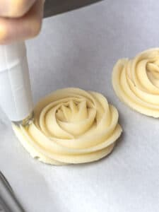 butter cookie dough being piped into rosettes with a piping bag