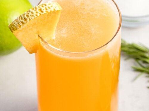 a glass of cantaloupe agua fresca with a slice of cantaloupe for garnish