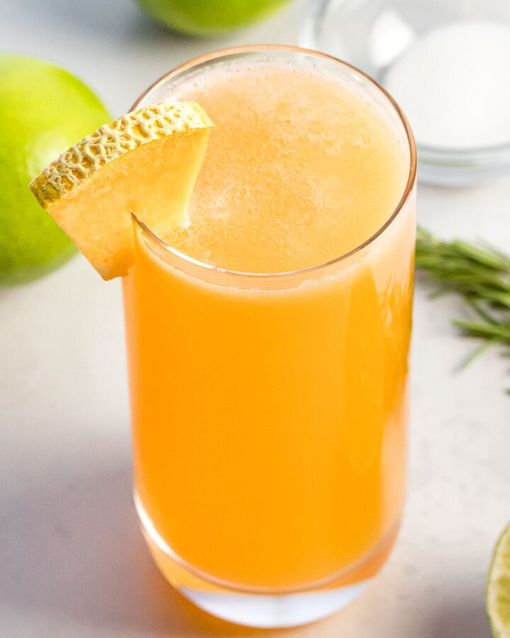 glass of cantaloupe agua fresca next to lime
