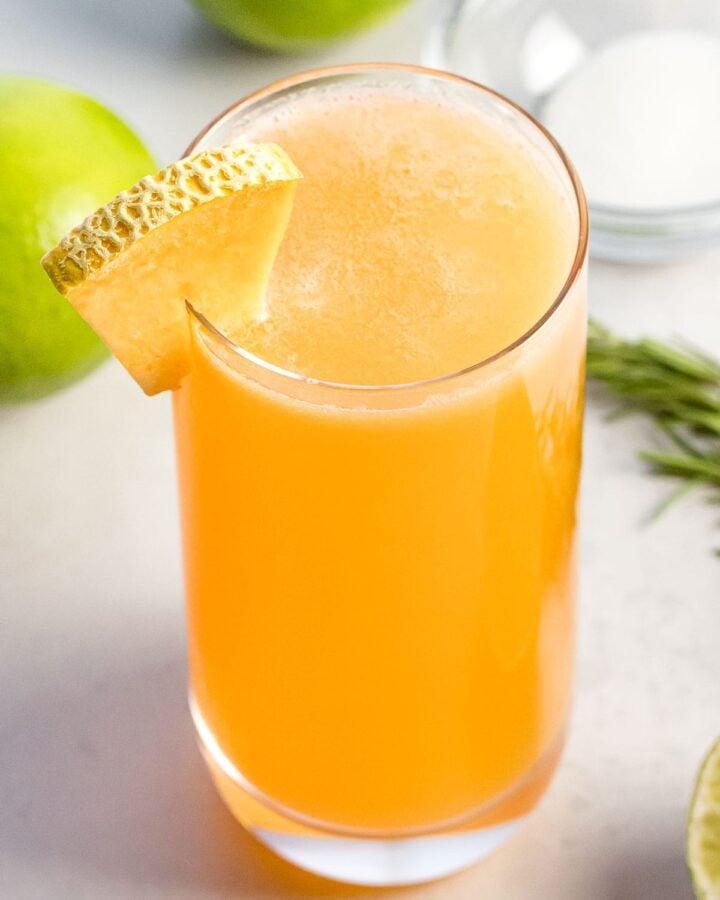 glass of cantaloupe agua fresca next to lime