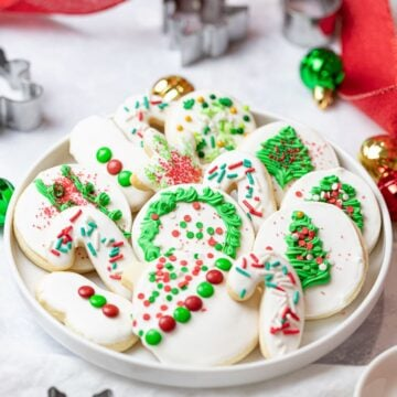 Christmas cut out cookies on a plate with sprinkles and royal icing decoration next to cookie cutters, ornaments, and red ribbon