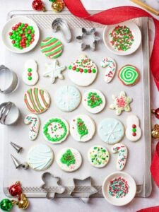 iced Christmas sugar cookies on a baking sheet next to ornaments, cookie cutters, and red ribbon