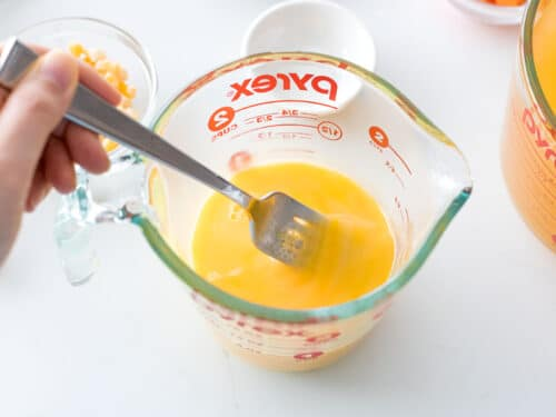 eggs being beaten in a measuring cup with a fork