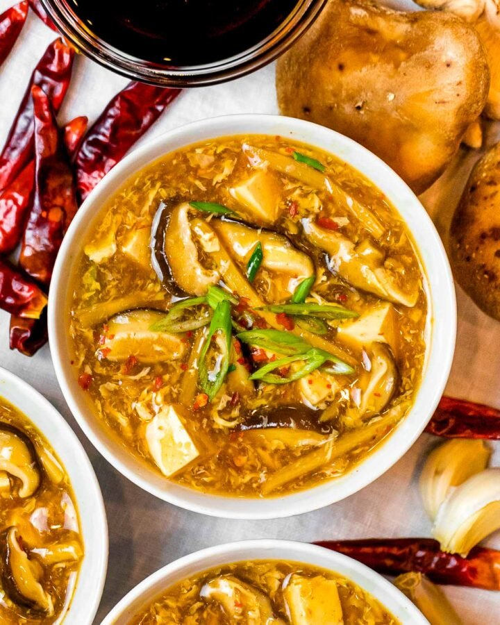 a bowl of Chinese hot and sour soup with mushrooms and tofu next to dried spicy chili peppers