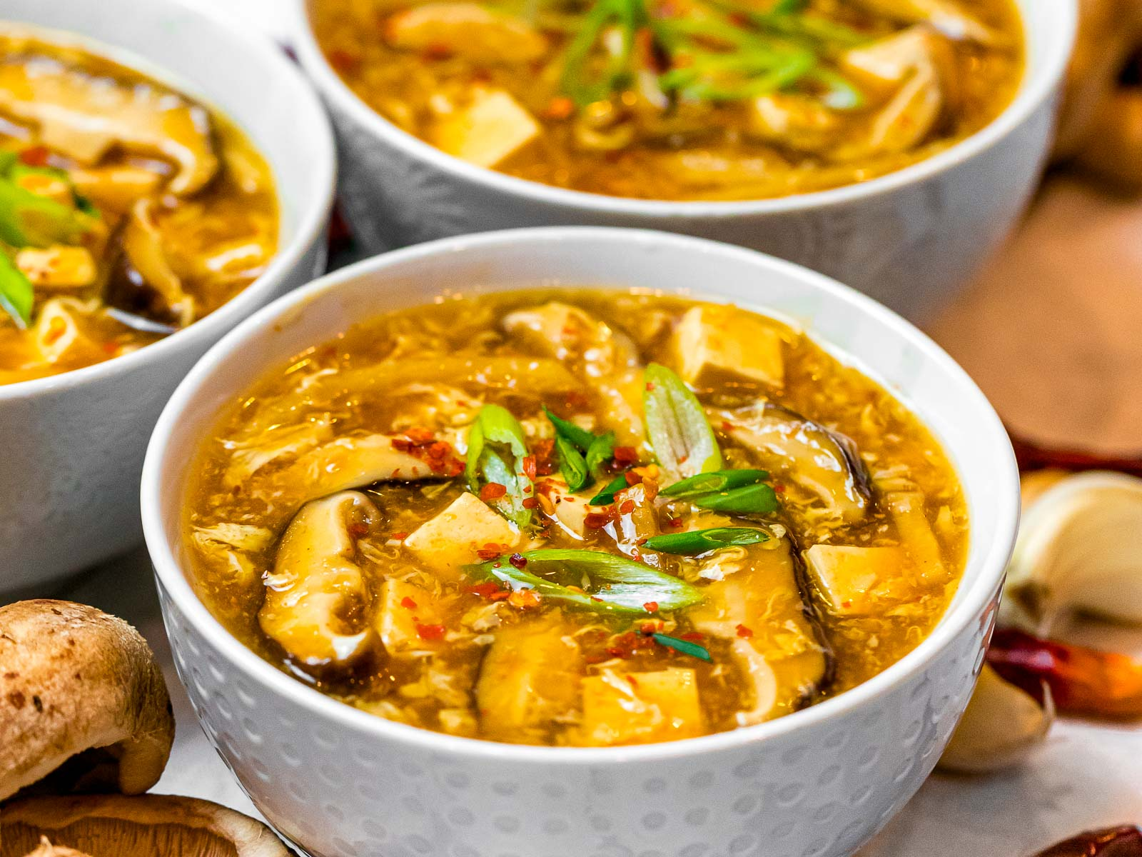 Chinese hot and sour soup with mushrooms, tofu, scallions, and red pepper flakes