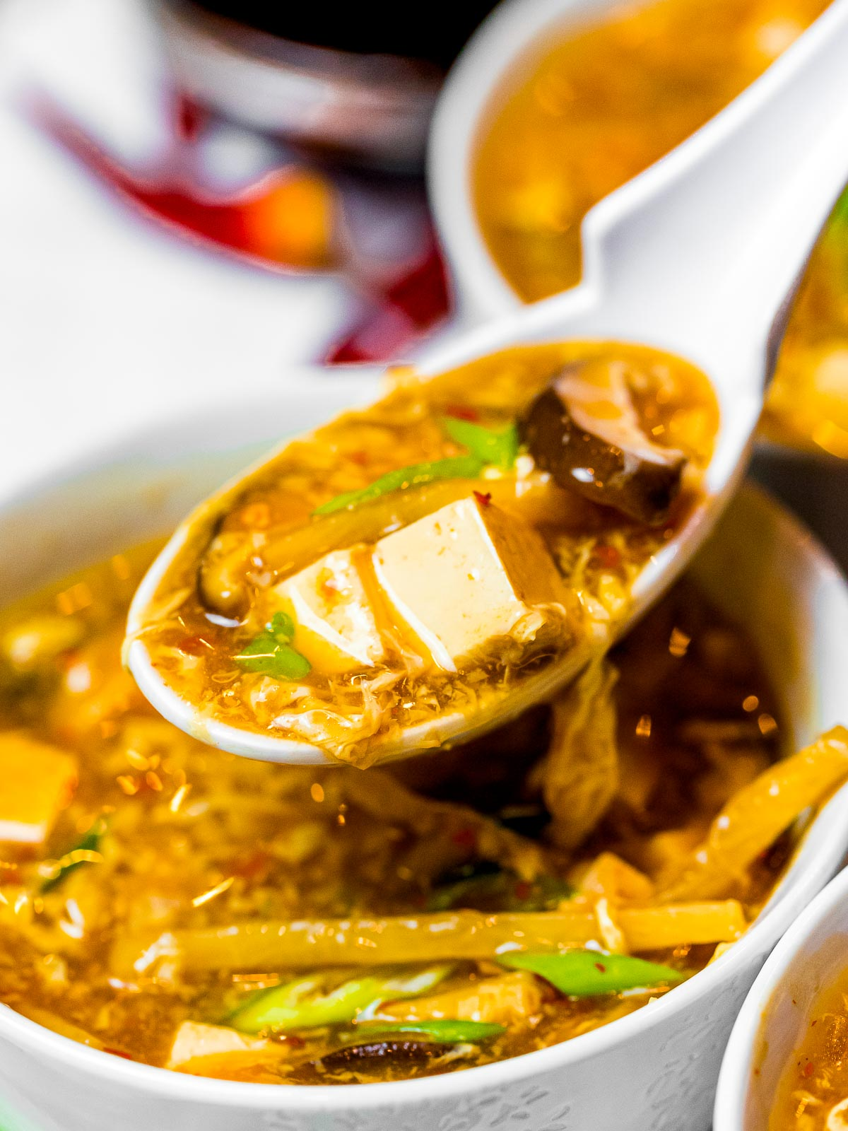 a spoonful of easy hot and sour soup with tofu, mushrooms, and bamboo shoots
