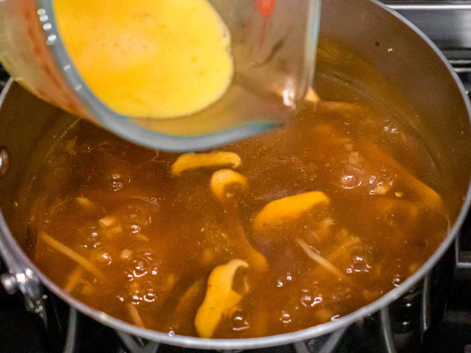 beaten eggs being added to hot and sour soup
